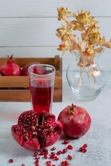 Vertikales foto von frisch geschnittenem granatapfel mit saft.