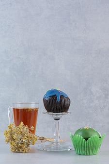 Vertikales foto von frischem duftendem tee mit muffins auf grau