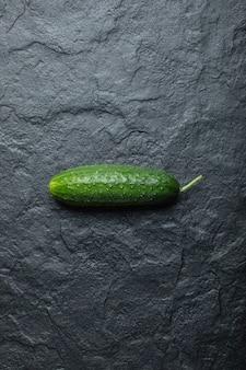 Vertikales foto von frischen bio-gurken auf schwarzem hintergrund.