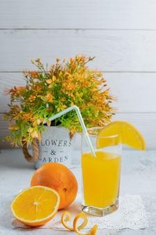 Vertikales foto von frischen bio-orangen mit einem glas saft.