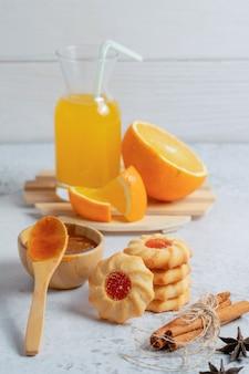 Vertikales foto von frischen hausgemachten keksen mit orange und marmelade.