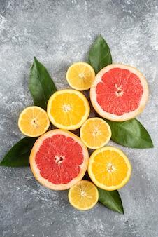 Vertikales foto von frischen zitrusfrüchten, halb geschnittene früchte mit blättern auf grauer oberfläche.