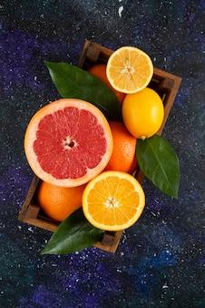 Vertikales foto von frischen zitrusfrüchten im holzkorb.