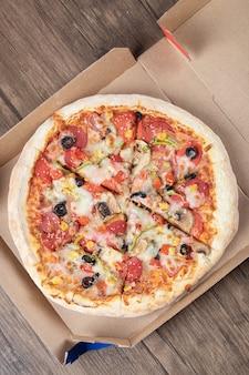 Vertikales foto von frischer gemischter pizza im pizzakarton über holztisch.