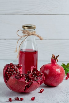 Vertikales foto von geschnittenen oder ganzen granatäpfeln mit einer flasche saft.