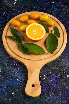 Vertikales foto von halb geschnittener orange mit blättern und kumquats.