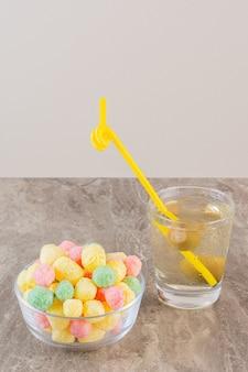 Vertikales foto von hausgemachten bunten bonbons mit cocktail auf grau.