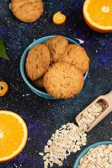 Vertikales foto von hausgemachten keksen in schüssel und orange mit haferflocken über dem boden.