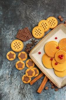 Vertikales foto von leckeren runden pfannkuchen auf teller und süßigkeiten auf grauem hintergrund
