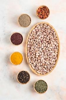 Vertikales foto von pile of beans mit verschiedenen gewürzen.