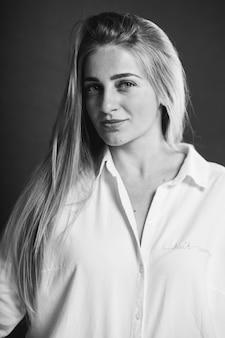 Vertikales graustufenporträt einer attraktiven kaukasischen blonden frau in einem weißen hemd posiert