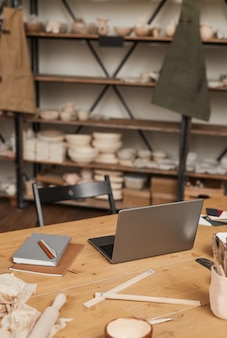 Vertikales hintergrundbild des laptops auf holztisch in leerer töpferwerkstatt, kleinunternehmenskonzept, kopierraum
