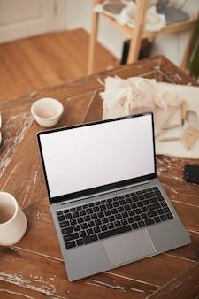 Vertikales hintergrundbild des laptops mit leerem weißen bildschirm auf dem tisch in der werkstatt, kleinunternehmen und unternehmertum, kopierraum