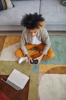 Vertikales hochwinkelporträt eines afroamerikanischen teenagers, der videospiele spielt, während er zu hause auf dem boden sitzt