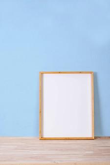 Vertikales holzrahmenmodell auf holzboden und hellblauem hintergrund