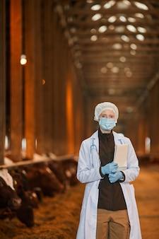 Vertikales hüftporträt des weiblichen tierarztes, der maske am bauernhof trägt und kamera betrachtet, während tablette hält