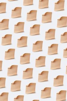 Vertikales kreatives muster von modellblättern des alten weinlese-pergamentpapiers auf einer weißen wand, kopienraum.