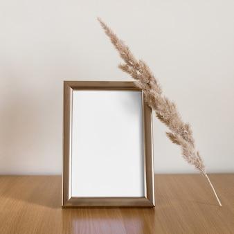 Vertikales leeres foto mit goldglänzendem rahmen und trockenem, flauschigem ast