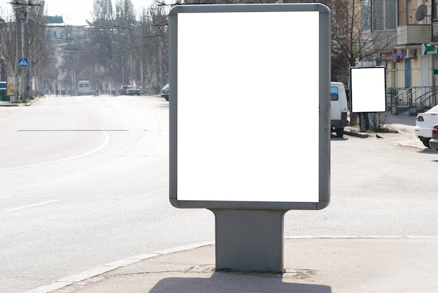 Vertikales leeres plakatweiß lokalisiert auf der stadtstraße