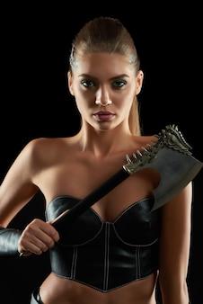 Vertikales nahaufnahmeporträt eines herrlichen weiblichen wikingers, der aggressiv mit einer axt auf der schwarzen wand schönheitsbrutalität wilder krieger amazonas-kulturkämpfer-kampfkleidwaffe aufwirft.