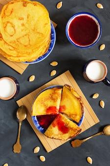 Vertikales obenliegendes foto von dünnen pfannkuchen des kürbises mit beerenmarmelade auf blauer platte