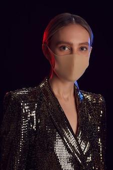 Vertikales porträt der blonden jungen frau, die partykleid und gesichtsmaske trägt, während gegen schwarzen hintergrund steht