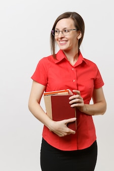 Vertikales porträt der business-lehrer-frau im roten hemd, rock und brille, die beiseite schaut und bücher in den händen hält, die auf weißem hintergrund isoliert sind. bildung oder lehre im hochschulkonzept.