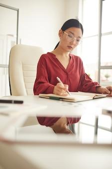 Vertikales porträt der eleganten asiatischen frau, die dokumente liest, während sie am schreibtisch im modernen weißen büro, weibliches chefkonzept, kopienraum arbeitet