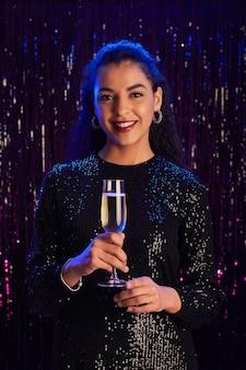 Vertikales porträt der eleganten jungen frau, die champagnergläser hält und an der kamera lächelt, während sie gegen funkelnden hintergrund an der partei aufwirft
