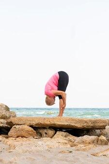 Vertikales porträt der frau mittleren alters, die yoga am strand praktiziert, das dehnen tut