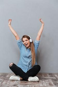 Vertikales porträt der glücklichen frau im hemd, das musik hört