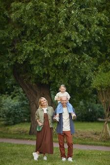 Vertikales porträt der glücklichen modernen familie, die im park zusammen mit dem niedlichen kleinen mädchen geht, das auf den schultern des vaters sitzt