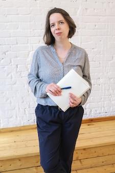 Vertikales porträt der jungen brunettefrau mit dem schulterlangen haar auf weißem backsteinmauerhintergrund. frau in einer grauen losen bluse steht mit notizbuch und stift in den händen.