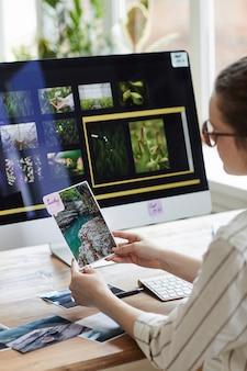 Vertikales porträt der jungen fotografin, die bilder hält und lächelt, während sie am schreibtisch mit fotobearbeitungssoftware auf computerbildschirm sitzt