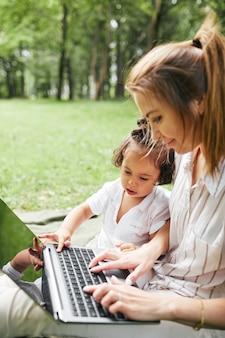 Vertikales porträt der jungen mutter mit laptop im freien beim spielen mit süßer tochter im park
