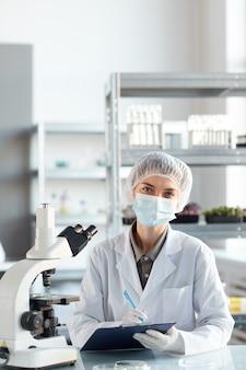 Vertikales porträt der jungen wissenschaftlerin, die gesichtsmaske trägt und kamera während der arbeit im labor betrachtet, kopieren raum oben