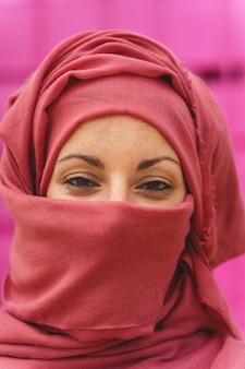 Vertikales porträt der muslimischen frau, die hiyab mit geöffneten augen trägt. kulturelle vielfalt und religion.