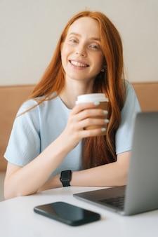 Vertikales porträt der nahaufnahme der glücklichen jungen schönen frau, die tasse mit heißem kaffee hält, der am schreibtisch mit laptop im café sitzt und kamera betrachtet. hübsche kaukasische dame der rothaarigen entfernt, die arbeitet oder studiert.