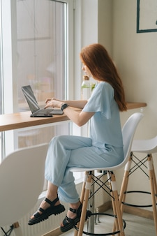 Vertikales porträt der schönen glücklichen jungen frau, die auf dem laptop sitzt, der am tisch am fenster im café sitzt und auf dem bildschirm schaut. hübsche kaukasische dame der rothaarigen entfernt, die arbeitet oder studiert.