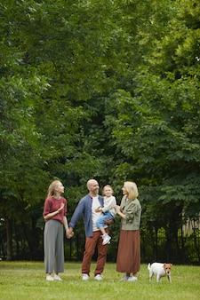 Vertikales porträt der sorglosen familie mit zwei kindern und haustierhund, die draußen auf grünem gras stehen, während sie zusammen im park spazieren gehen