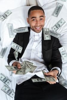 Vertikales porträt des afrikanischen mannes im anzug, der auf bett im hotelzimmer liegt und das geld wirft. draufsicht