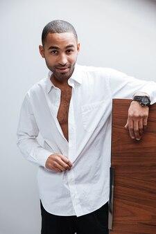 Vertikales porträt des afrikanischen mannes kleidet sich im hotelzimmer und betrachtet kamera