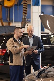 Vertikales porträt des automechanikers, der mit geschäftsmann spricht, während digitales tablett in autowerkstatt verwendet wird