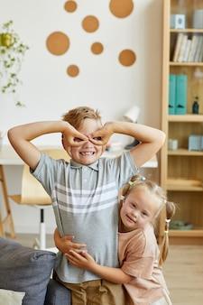 Vertikales porträt des glücklichen jungen, der gesichter an der kamera macht, die vorgibt, superheld mit der kleinen schwester mit down-syndrom zu sein, die ihn umarmt
