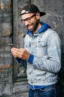 Vertikales porträt des hippie-kerls im denimhemd, -kappe und -eyewear, die modernes telefon in seinen händen halten