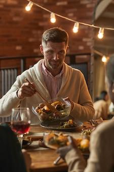 Vertikales porträt des hübschen reifen mannes, der essen dient, während dinnerparty mit freunden und familie veranstaltet
