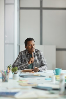 Vertikales porträt des jungen afroamerikanischen mannes, der nachdenklich wegschaut, während er kreative ideen auf notizblock im büro, kopierraum schreibt