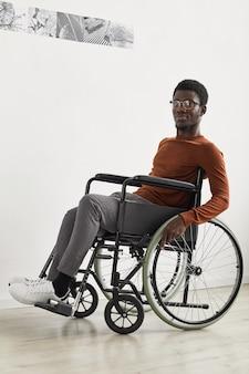 Vertikales porträt des jungen afroamerikanischen mannes in voller länge, der rollstuhl benutzt und während der galerieausstellung der modernen kunst erkundet