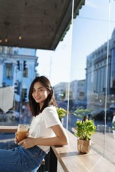 Vertikales porträt des jungen asiatischen weiblichen modells, das kaffee im café nahe fenster trinkt