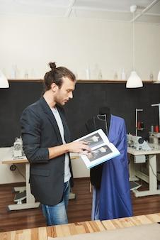 Vertikales porträt des jungen erfolgreichen professionellen männlichen schneiders, der an blauem kleid für kunden arbeitet und sich an einige nähtechniken erinnert, indem er durch tutorialbuch schaut.